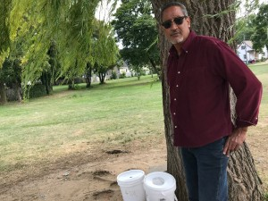 Rudy Rivera of the Father Tracy Health and Wellness Center stands next to buckets placed by volunteers and to be used as a receptacle for used needles at a lot on North Clinton Avenue. Photo by Patti Singer/LaVoz