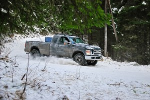 Pickup truck rides winter snow road in a pine forest
