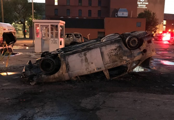 An overturned and burned car in the parking lot across from the Public Safety Building, May 30, 2020. Photo by Patti Singer/Minority Reporter Media Group